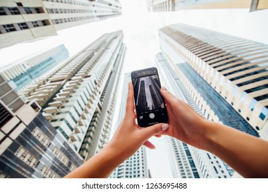 DUBAI, UAE - NOVEMBER 2018: Close up of woman hands take phone on the phone of skycrapers in modern arhitecture city.