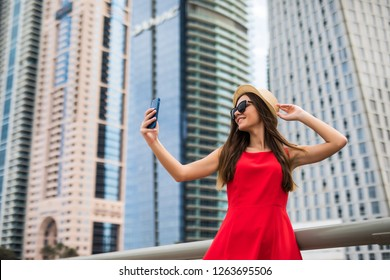 DUBAI, UAE - NOVEMBER 2018: Portrait of young woman in red dress, sunglasses and summer hat take selfie on the phone on downtown skycrapers background