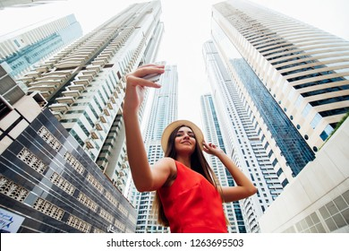 DUBAI, UAE - NOVEMBER 2018: Young woman in red dress and summer hat take selfie photo on the phone with modern skycrapers on background.