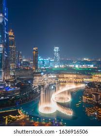 DUBAI , UAE - NOVEMBER 2019: Amazing view of the dancing fountain in Dubai Mall next to Burj Khalifa in Downtown Dubai; Night Cityscape View