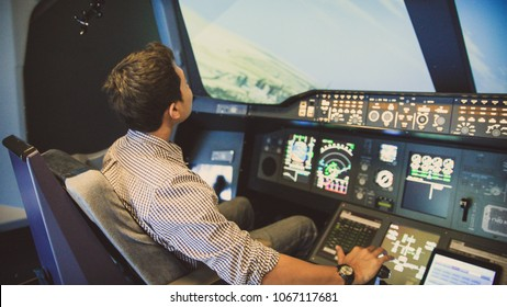 DUBAI, UAE - NOVEMBER 22, 2016: Asian men play a plane simulator at the Emirates simulation counter located in the Mall of Dubai.