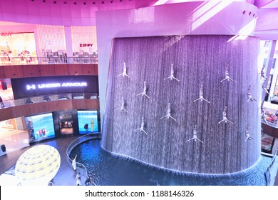 DUBAI, UAE - NOVEMBER 22, 2017: Shoppers visit the Human Waterfall art piece at Dubai Mall. It is the largest mall in the world by total area with 502,000 square metres retail area.
