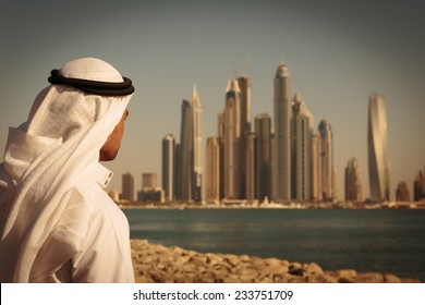 DUBAI, UAE - NOVEMBER 7: Modern buildings in Dubai Marina,, UAE. In the city of artificial channel length of 3 kilometers along the Persian Gulf. Man in Arab dress looks at the city. Toned
