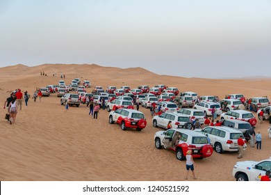 Dubai, UAE - Oct 10, 2018: Tourists and large group of Toyota Landcruiser 4WD parked on the dunes as part of a desert safari in Dubai