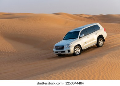 Dubai, UAE - Oct 10, 2018: Toyota Landcruiser 4WD driving through dunes, also called dune bashing as part of a desert safari in Dubai