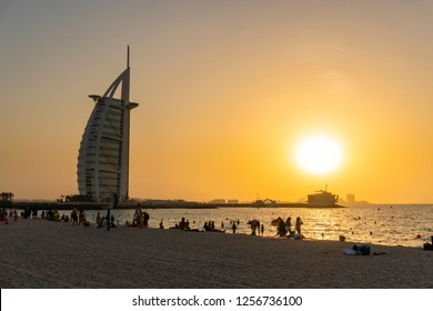 Dubai, UAE - Oct 13, 2018: View of people at the Jumeirah Beach at sunset, with view of Burj Al Arab