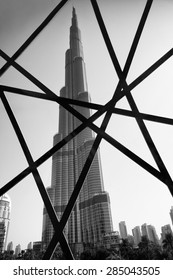 DUBAI, UAE - OCTOBER 22, 2014: The modern steel Burj Khalifa tower, whose design is patterned after traditional Islamic architecture, viewed from behind a window at the Dubai Mall.