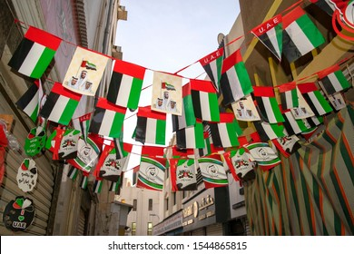 Dubai / UAE - October 25, 2019: Many UAE flags on old Dubai city background. Old Dubai street decorated with national flags for Emirates National Day Celebration.