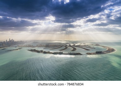 Dubai, UAE. Palm Jumeirah geometric shapes from helicopter at sunset with clouds.