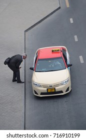 DUBAI, UAE - SEPTEMBER 15, 2017: A man bends down to the taxi with a red roof in Dubai, United Arab Emirates