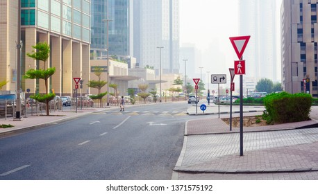 DUBAI, UAE - SEPTEMBER 25 2018: give way sign on the road in city with modern buildings background