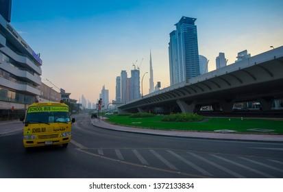 DUBAI, UAE - SEPTEMBER 26 2018: Dubai city downtown and school bus moving on the road