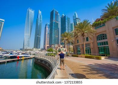 DUBAI, UAE - SEPTEMBER 27 2018: old tourist man taking photos of Dubai Marina city downtown