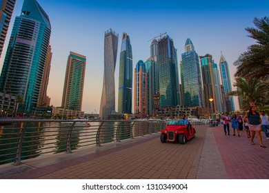 DUBAI, UAE - SEPTEMBER 29 2018: small red car driving in Dubai Marina city with skyscrappers in background
