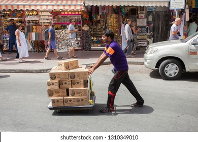 DUBAI, UAE - SEPTEMBER 29 2018: man with delivery package on the street in Dubai city