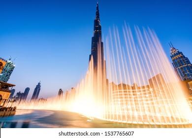 Dubai, UAE / United Arab Emirates - August 29 2018: Fountains in Dubai mall overlooking Dubai cityscape and buildings