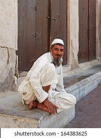 DUBAI, UAE-OCTOBER 30: Old man sitting on the stone steps of the old city of Bar Dubai on October 30, 2013. It is the oldest part of the city in Dubai, UAE