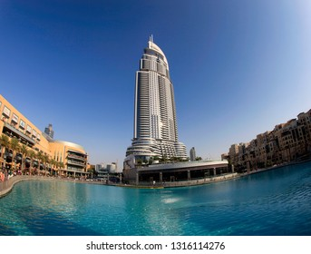 Dubai, United Arab Emirates, 02.21.2014 Sunny day in the city, a high-rise building in the center and a water fountain