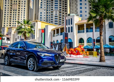 Dubai / United Arab Emirates - 02/25/2018: The front of the Alfa Romeo Stelvio SUV car is seen in the Jumeirah Beach Residence district of Dubai Marina with skyscrapers in the background