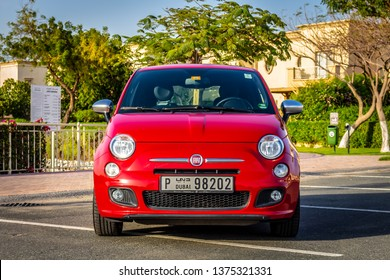 Dubai, United Arab Emirates - 03/30/2019: The front of a Fiat 500 Sport next to a park in Dubai, UAE. Trees against a lake are visible in the background.