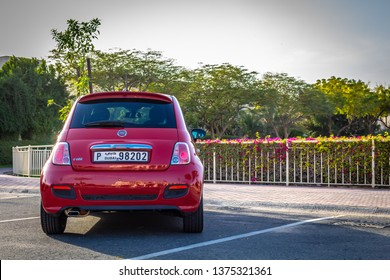 Dubai, United Arab Emirates - 03/30/2019: The back of a Fiat 500 Sport next to a park in Dubai, UAE. Trees against a lake are visible in the background.