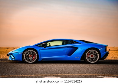 Dubai / United Arab Emirates - 04/05/2018: The Lamborghini Aventador S supercar on a quiet Dubai road in the desert, in front of a red Fiat 500