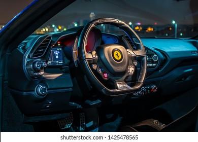 Dubai, United Arab Emirates - 06/14/2019: Luxury interior steering wheel, with prancing horse logo visible, and dashboard of Ferrari 488 Spider convertible supercar at night