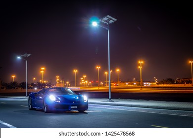Dubai, United Arab Emirates - 06/14/2019: Front view of Ferrari 488 Spider convertible supercar parked at night on a Dubai street