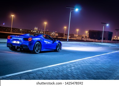 Dubai, United Arab Emirates - 06/14/2019: Rear view of Ferrari 488 Spider convertible supercar parked at night on a Dubai street