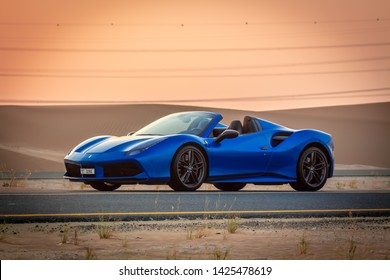 Dubai, United Arab Emirates - 06/14/2019: Front view of Ferrari 488 Spider convertible supercar parked on a Dubai street in the desert at sunset