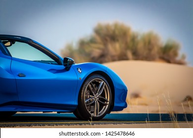 Dubai, United Arab Emirates - 06/14/2019: Front of Ferrari 488 Spider convertible supercar parked on a Dubai street in the desert at sunset