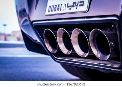 Dubai / United Arab Emirates - 08/16/2018:  The exhaust pipes on a supercar or sports car shown against the background of an empty road. A Dubai number plate is partially visible.