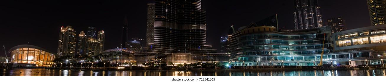 DUBAI, UNITED ARAB EMIRATES - 10 SEPTEMBER 2017: Panorama of lights of Dubai Downtown skyscrapers around Dubai Fountains at Burj Khalifa