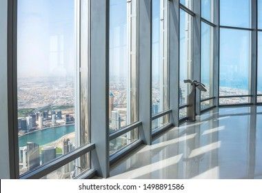 Dubai, United Arab Emirates - 13 MAY 2019: Monitor of computer by the window in Burj Khalifa with an amazing view of skyscraper over the city.