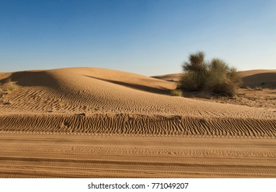 Dubai, United Arab Emirates, 29 November 2017: car traces in the yellow sand of Dubai desert