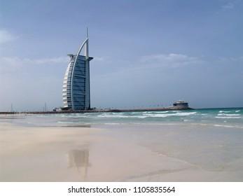 "Dubai, United Arab Emirates - April 12, 2004: hotel ""Burj al Arab"" reflects in the water over a white sandy beach"