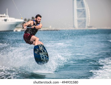 Dubai, United Arab Emirates - Circa 2015 - Wakeboarder enjoying a perfect day in Dubai Marina with Burj Al Arab in the background