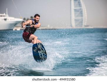 Dubai, United Arab Emirates - Circa 2015 - Wakeboarder enjoying a perfect day in Dubai Marina with Burj Al Arab in the background