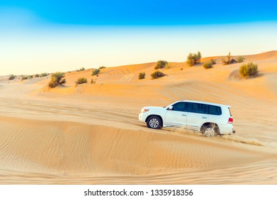 DUBAI, UNITED ARAB EMIRATES - DECEMBER 13, 2018: White jeep in the desert. Copy space for text