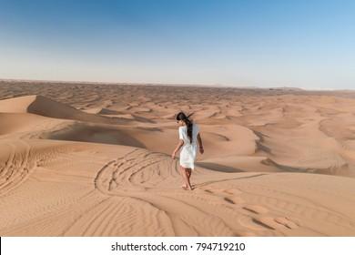 42d04172c19 Dubai United Arab Emirates Desert , Woman with white dress walking in the  Dubai desert sand
