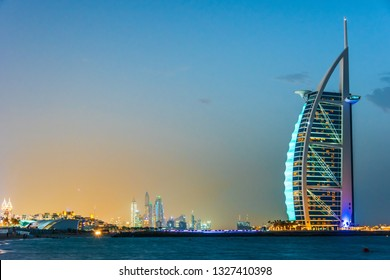 DUBAI, UNITED ARAB EMIRATES - FEB 11, 2019: The Burj Al Arab or Tower of the Arabs, a luxury hotel in Dubai with Marina Towers in background, United Arab Emirates.