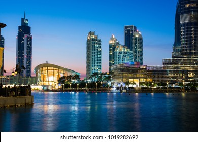 DUBAI, UNITED ARAB EMIRATES - FEBRUARY 5, 2018: Dubai Opera and modern Dubai downtown skyscrapers reflected in the water at blue hour