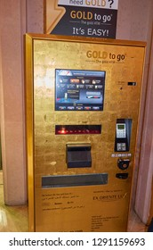 Dubai, United Arab Emirates - February 2014: Gold coins and bars dispensing ATM machine in shopping mall of Dubai, where you can buy gold with a Credit card or Cash from a machine.