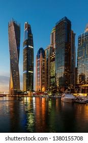 Dubai, United Arab Emirates - February 14, 2019: Dubai marina modern scene of skyscrapers and luxury yachts at blue hour