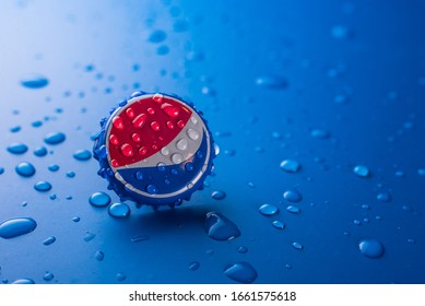 Dubai, UNITED ARAB EMIRATES - February 20, 2020: classic cap close-up of Pepsia-Cola on a blue background with drops of water.