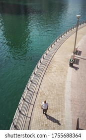 Dubai / United Arab Emirates - February 1, 2020: aerial photo of Western man walking along water canal in Dubai Marina during day time