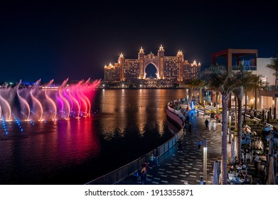 Dubai, United Arab Emirates - February 1, 2021: Music and lights fountain show with Atlantis the Palm hotel view from the Pointe waterfront dining and leisure destination at Palm Jumeirah in Dubai
