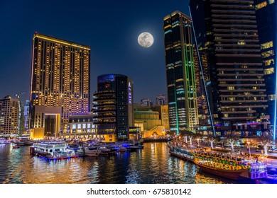 Dubai, United Arab Emirates - February 9, 2017 - View of the Dubai marina at night with a big moon