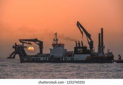 Dubai, United Arab Emirates - January 23, 2018: Self propelled dredger Athena in the sea at sunset.