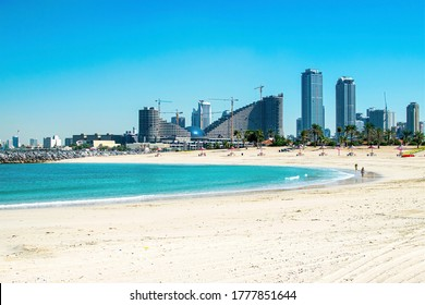 Dubai, United Arab Emirates January 16, 2020: People on the beautiful public beach with turquoise water and a white sand in Persian Gulf shoreline, Dubai. View of Sharjah Skyscraper.